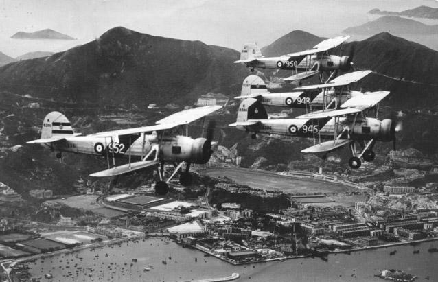 824 Squadron Swordfish from HMS Eagle on Coronation Flypast over Hong Kong (Happy Valley racecourse in background).  Pilot of 945 with black flight leader's marking on tail is Sqn Ldr AB Woodhall and crew is L/Tel Faulkner and Lt Gardner.  Photo taken  0825, May 12, 1937.